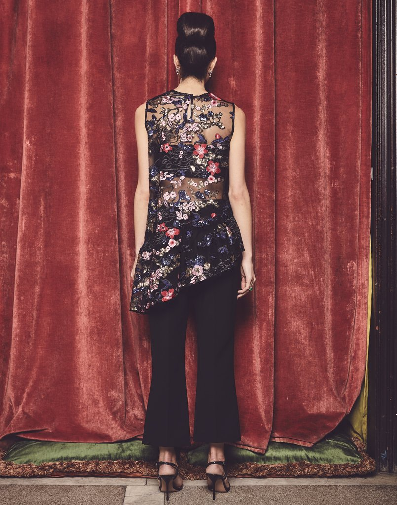 Model displays back of tank top with gorgeous flower embroidery, glittering sequins, and uneven ruffle hem