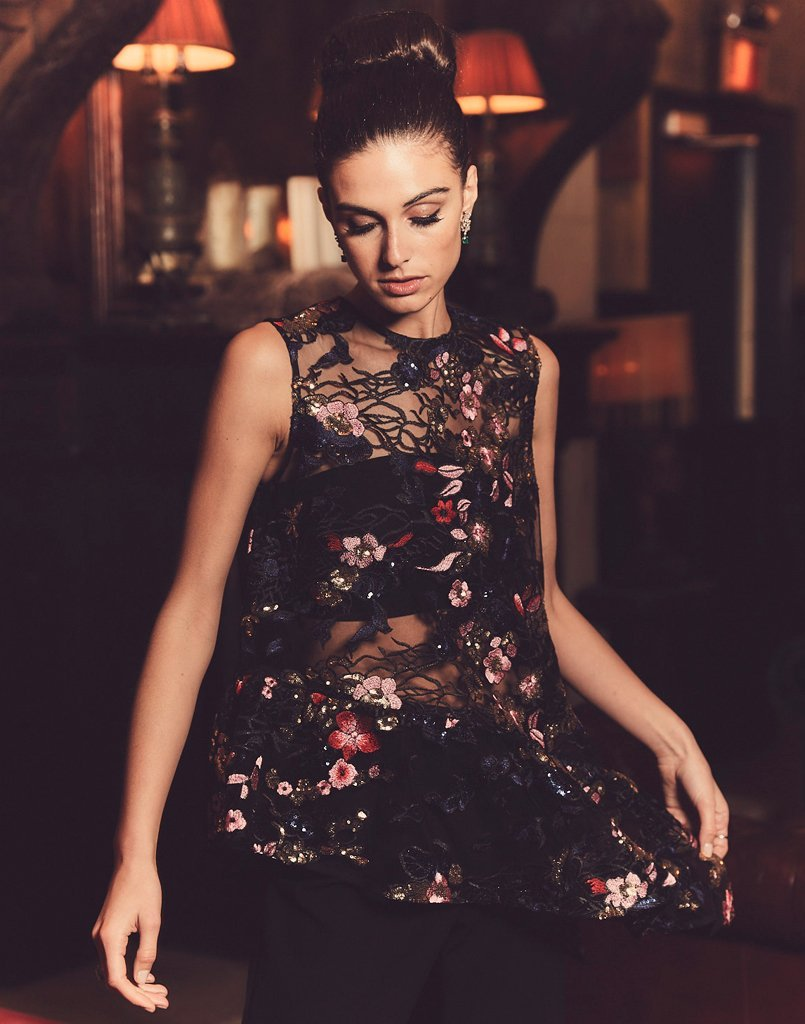 Glamorous woman wears mesh tank top with a ruffle edge and gorgeous embroidered flowers and sequins