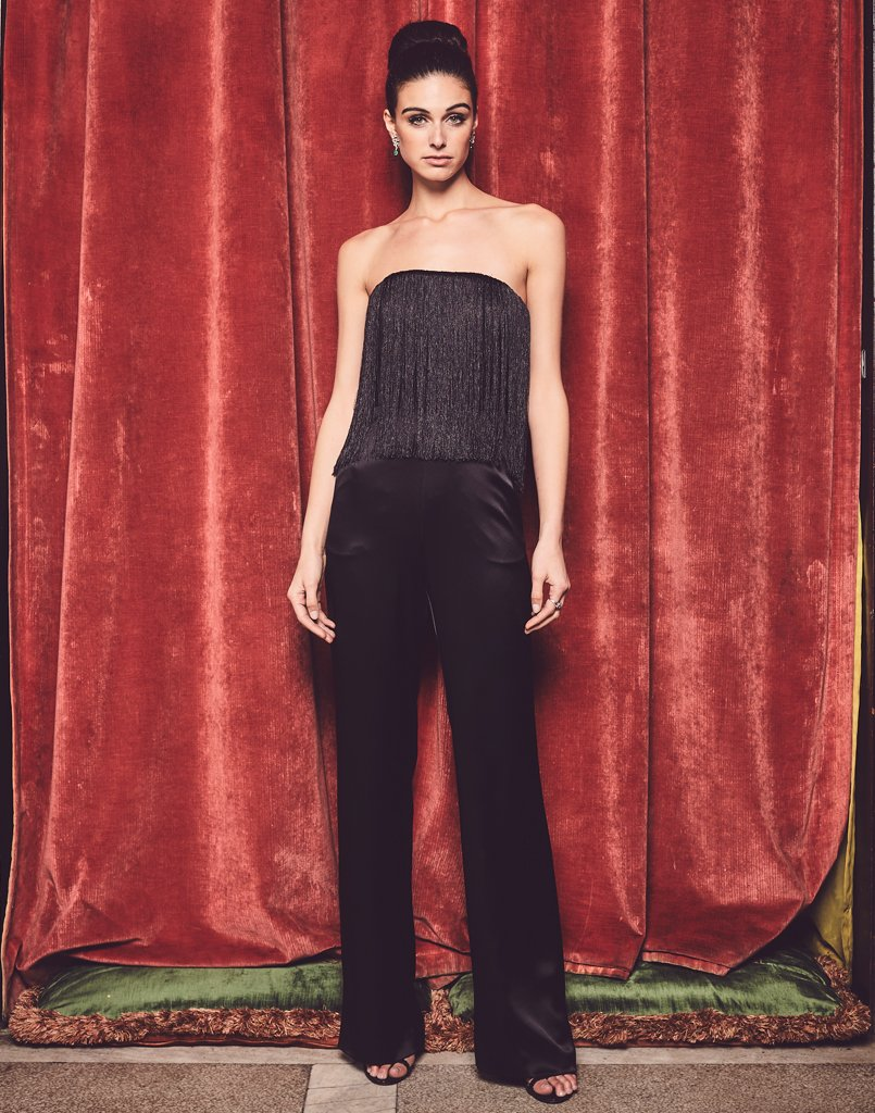 Model against red backdrop wearing black fringe jumpsuit with pockets
