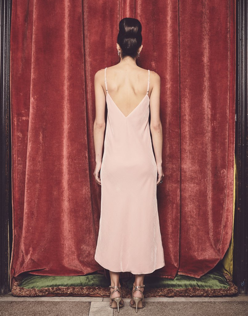 Back view of velvet dress showcases dip in the back and midi length