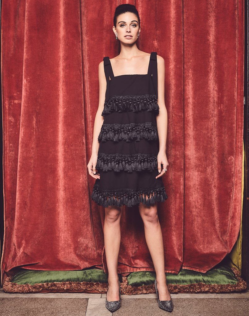 Model against red backdrop wearing a black chiffon tassel dress