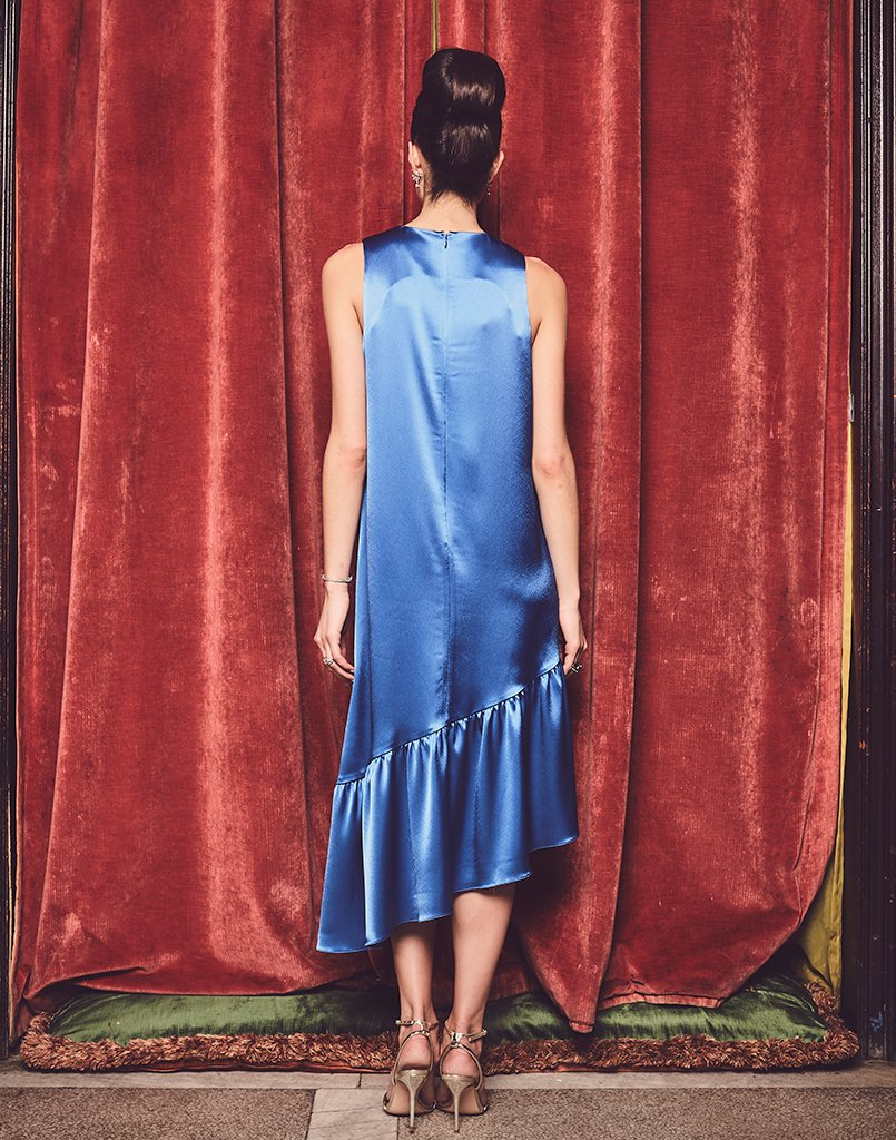 Back of midi dress in bright sapphire blue with ruffle detailing along the hem.