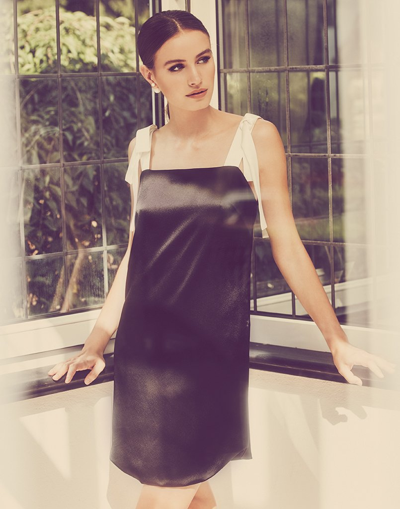 Fabulous woman stuns in the perfect little black dress, with white straps that make it a glamorous choice for summer.