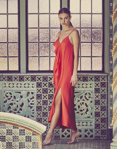 Model shows off leg slit in couture cherry red midi dress with draped center.