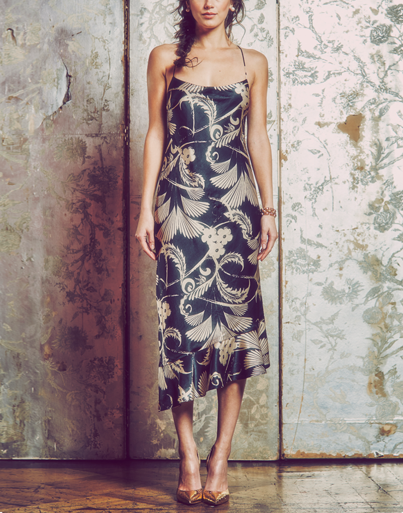 midi slip dress, bias cut, signature Mestiza black and champagne gold satin silk print, cowl neckline, asymmetric ruffle hem, criss cross tie back, camouflaged motto