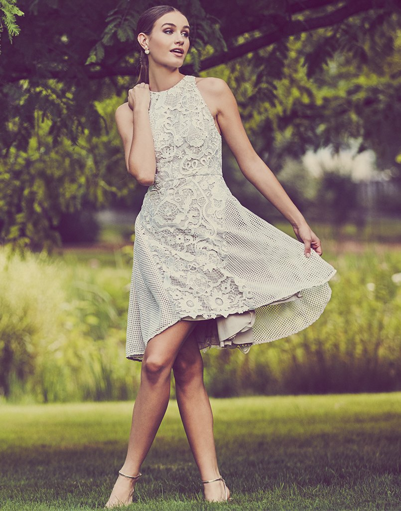 As woman walks through park she swings her dress, showing off the beautiful white color and lace detailing.