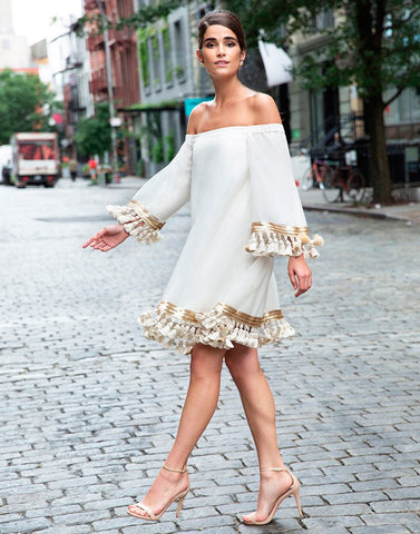 Gorgeous model walks down the streets of New York while her white long sleeve summer dress flairs around her with tassels swinging.