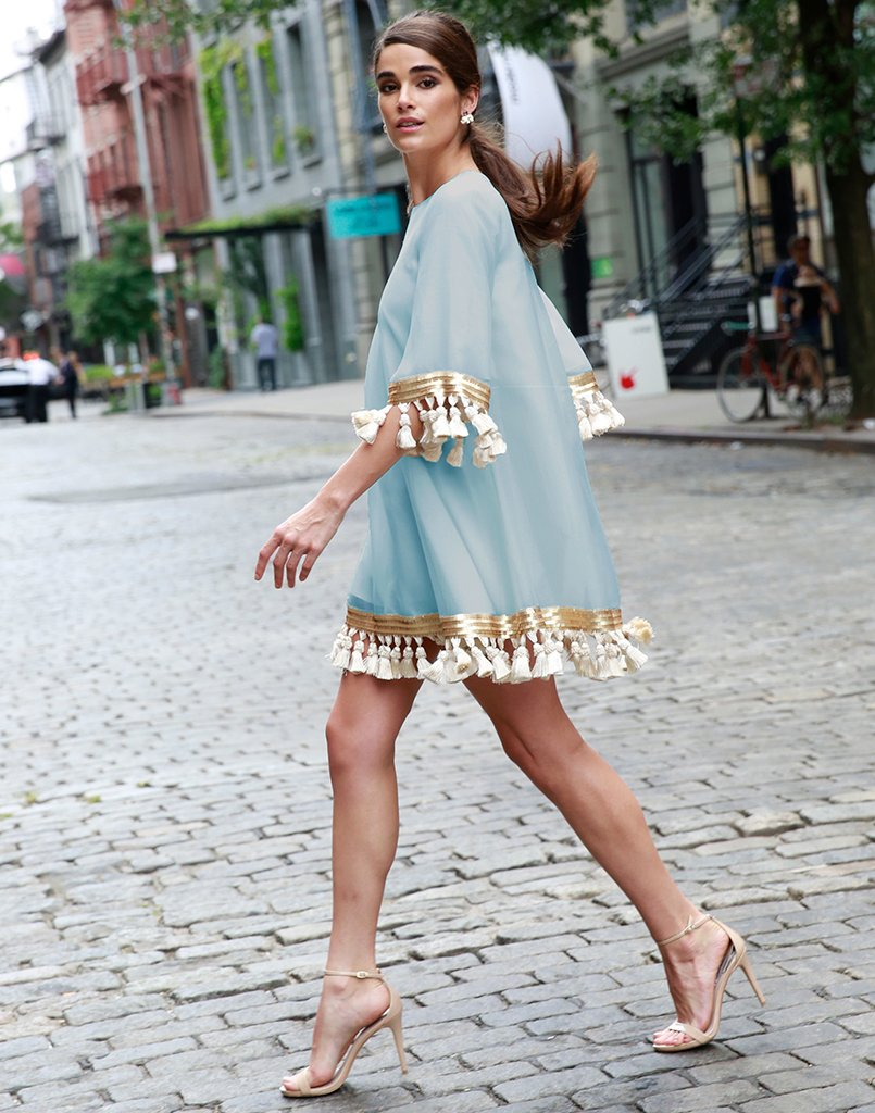 Gorgeous older woman walks through New York City in a blue long sleeved dress that is glamorous and classy, perfect for vacations in Europe.