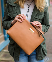 Close-up of model unzipping the Lyra Tablet Clutch Bag in brown vegan leather