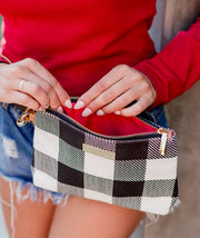 Close-up of a model opening the Aquila Clutch Bag in Buffalo Check