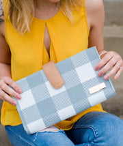 Model posing with the Juno Diaper Clutch Bag in Gray Buffalo Check on her lap