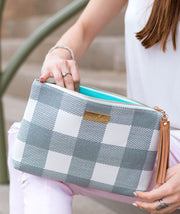 Model opening the Lyra Table Clutch Bag in Gray Buffalo Check