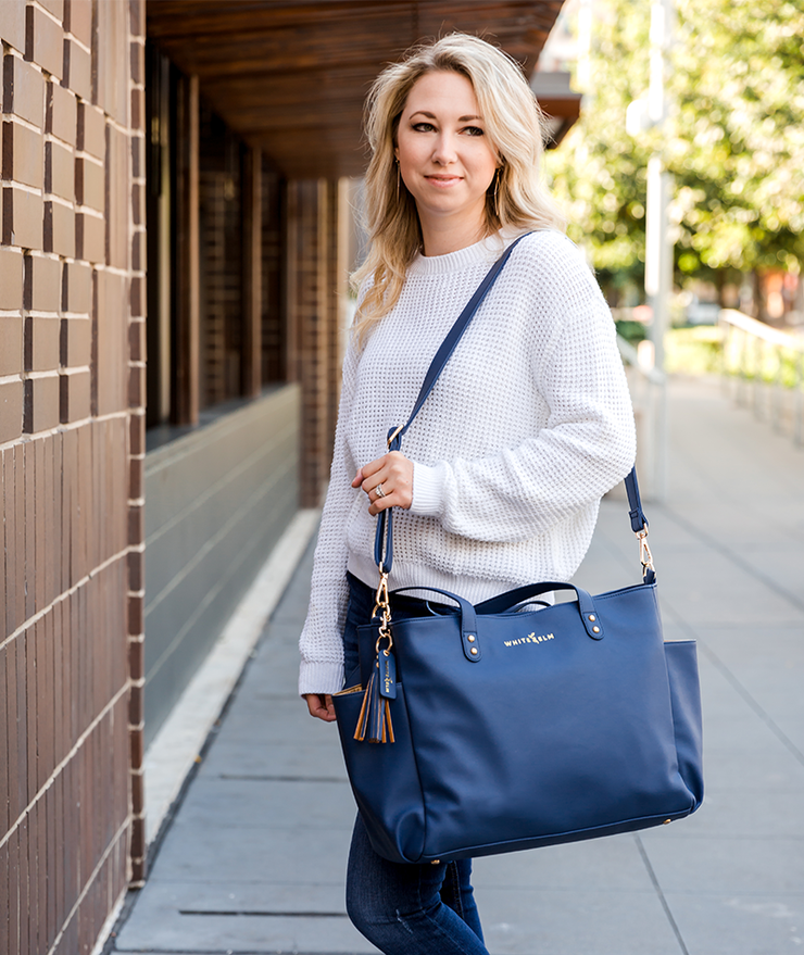 Navy blue vegan leather White Elm Aquila tote bag carried with long crossbody strap