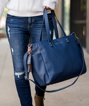 Navy blue vegan leather White Elm Aquila tote bag carried with shoulder straps