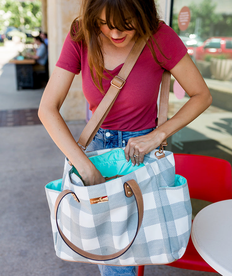 Model looking into the Aquila gray buffalo plaid tote bag by White Elm