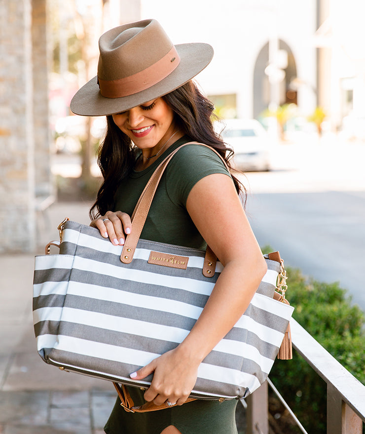 white elm aquila tote bag in gray stripes water resistant canvas held over shoulder