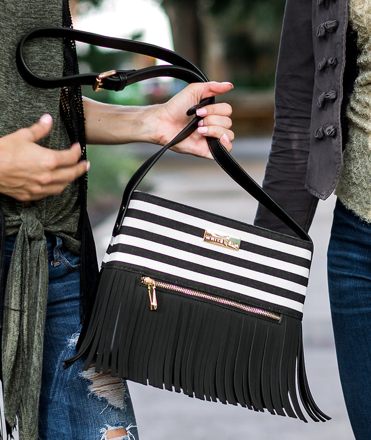 Model holding the Black Stripes Boho City Fringe Crossbody Bag