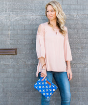 Model posing against a wall with the Crosses Clutch Bag in blue around her wrist