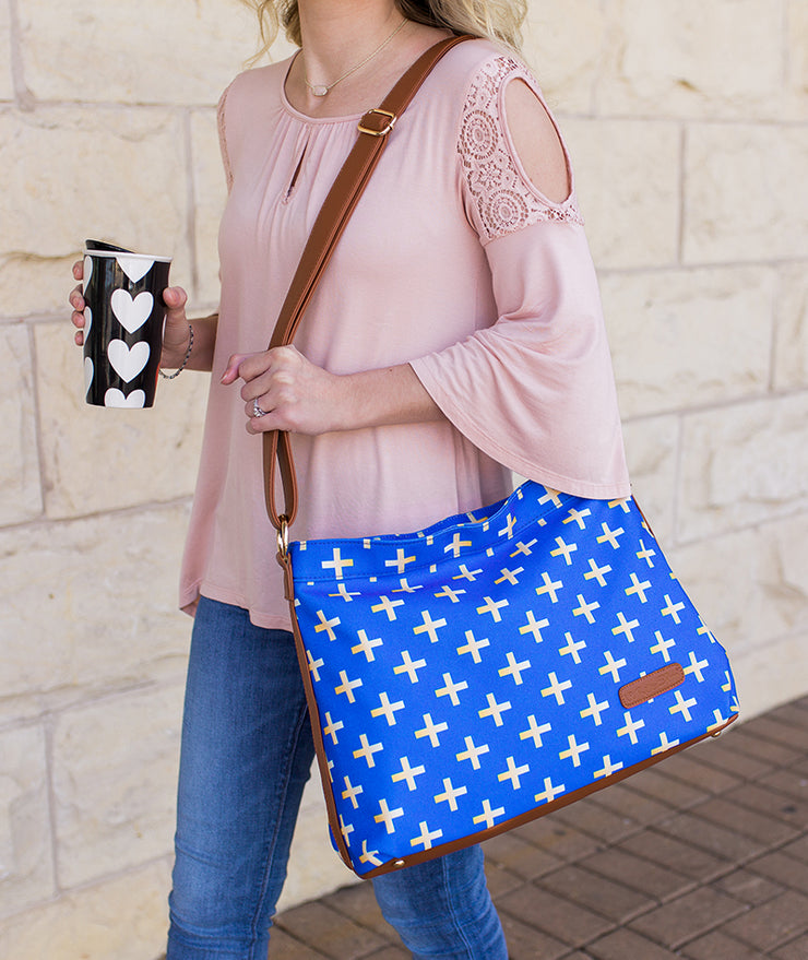 Woman walking with the Crosses Hobo Crossbody Bag in blue over her shoulder