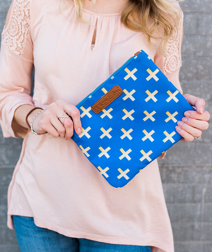 Close-up of model holding the Crosses Clutch Bag in blue in front of herself