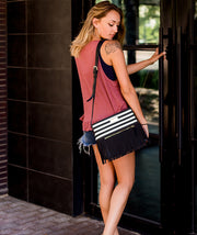model holding boho city fringe bag by white elm in black stripes