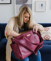 Woman sitting on a couch while looking through her burgundy Aquila Tote Bag.