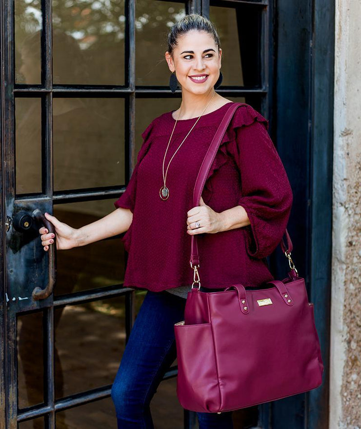 vegan leather tote bag worn crossbody in burgundy red
