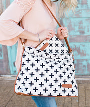 Woman pulling a matching clutch out of the Crosses Hobo Crossbody Bag in white