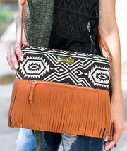Model posing with her hand on the Aztec Boho City Fringe Crossbody Bag, worn across the body