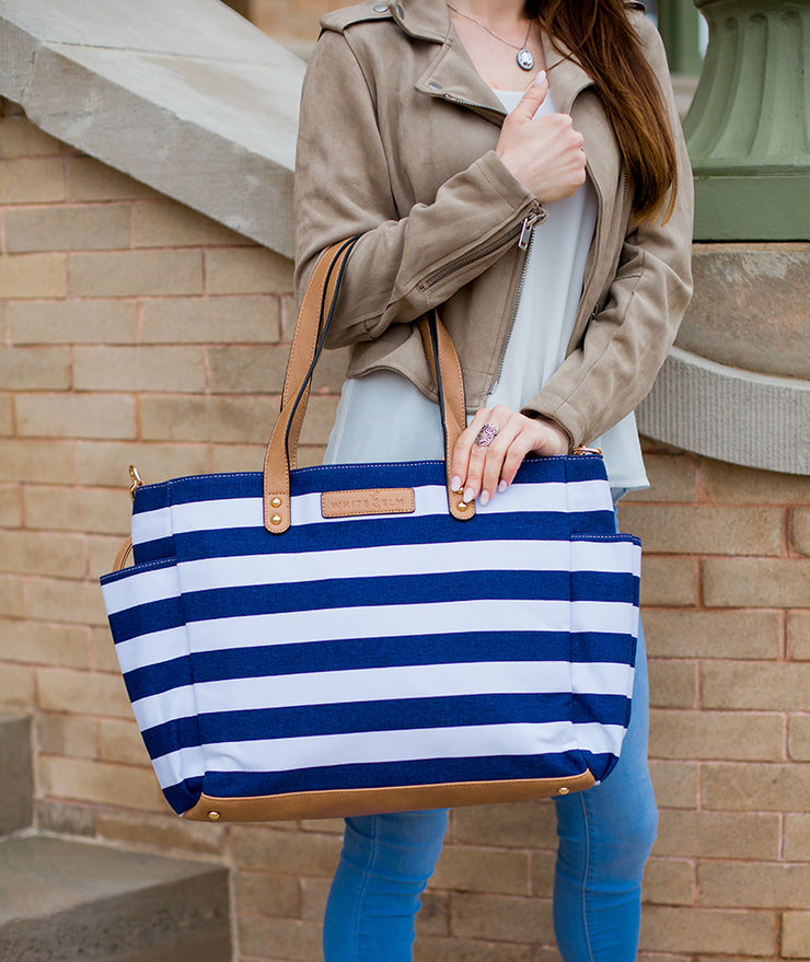 Model carrying Aquila Tote Bag In Navy Blue Stripe