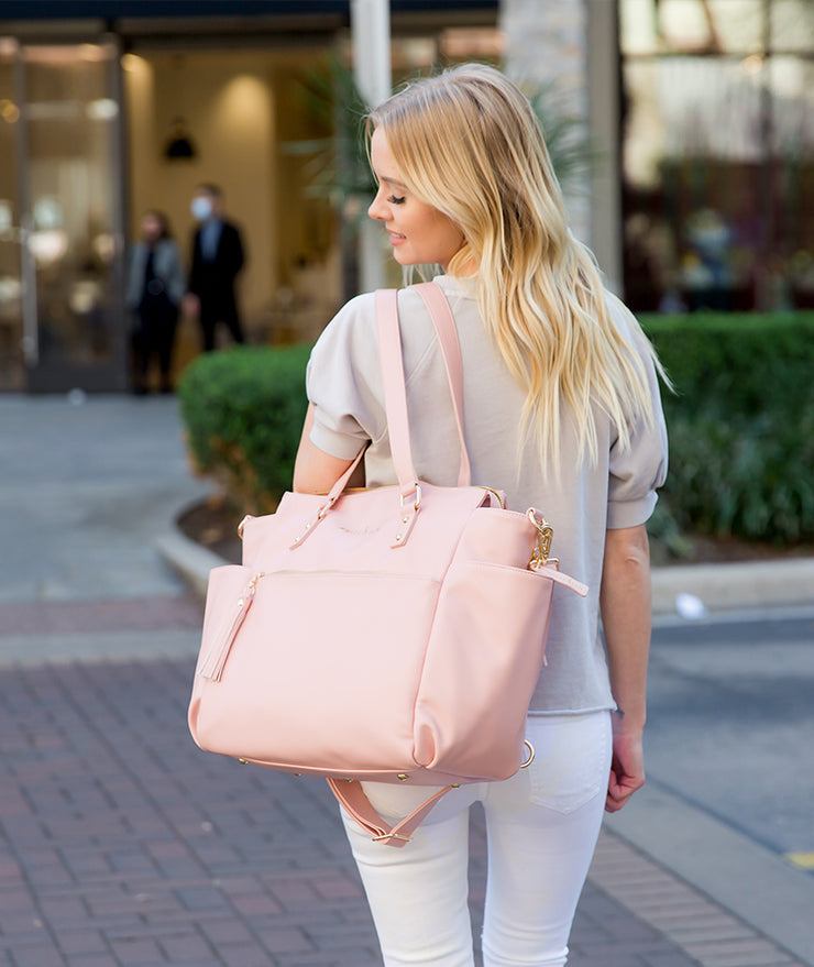 Gemini convertible backpack in pink vegan leather by white elm worn over shoulder