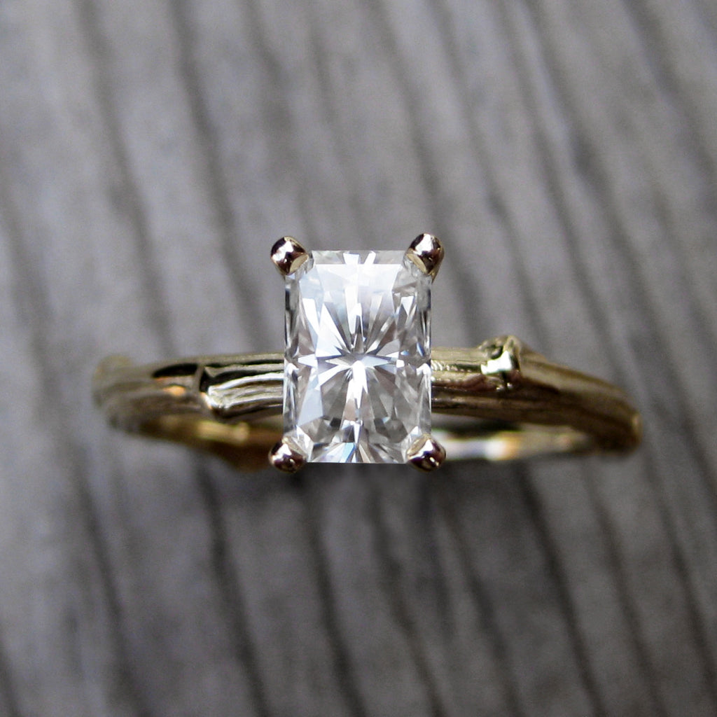 Yellow gold twig solitaire engagement ring with a Forever One radiant cut moissanite