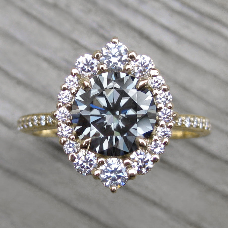 2ct vintage inspired yellow gold halo with a grey moissanite center and conflict-free diamond band