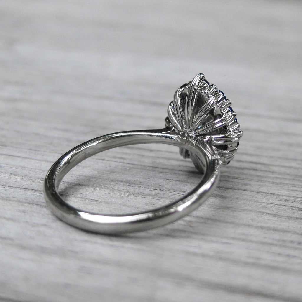Back side of oval moissanite and sapphire halo engagement ring with leaf-life gallery wires in white gold
