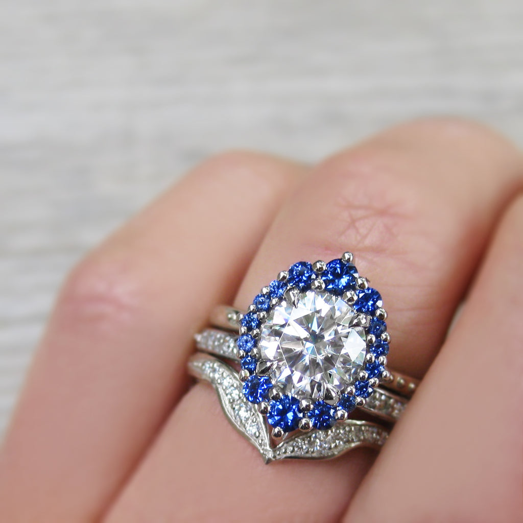 Antique-Inspired Halo Engagement Ring with a Forever One Moissanite Center with a Blue Sapphire Halo stacked with two diamond wedding bands