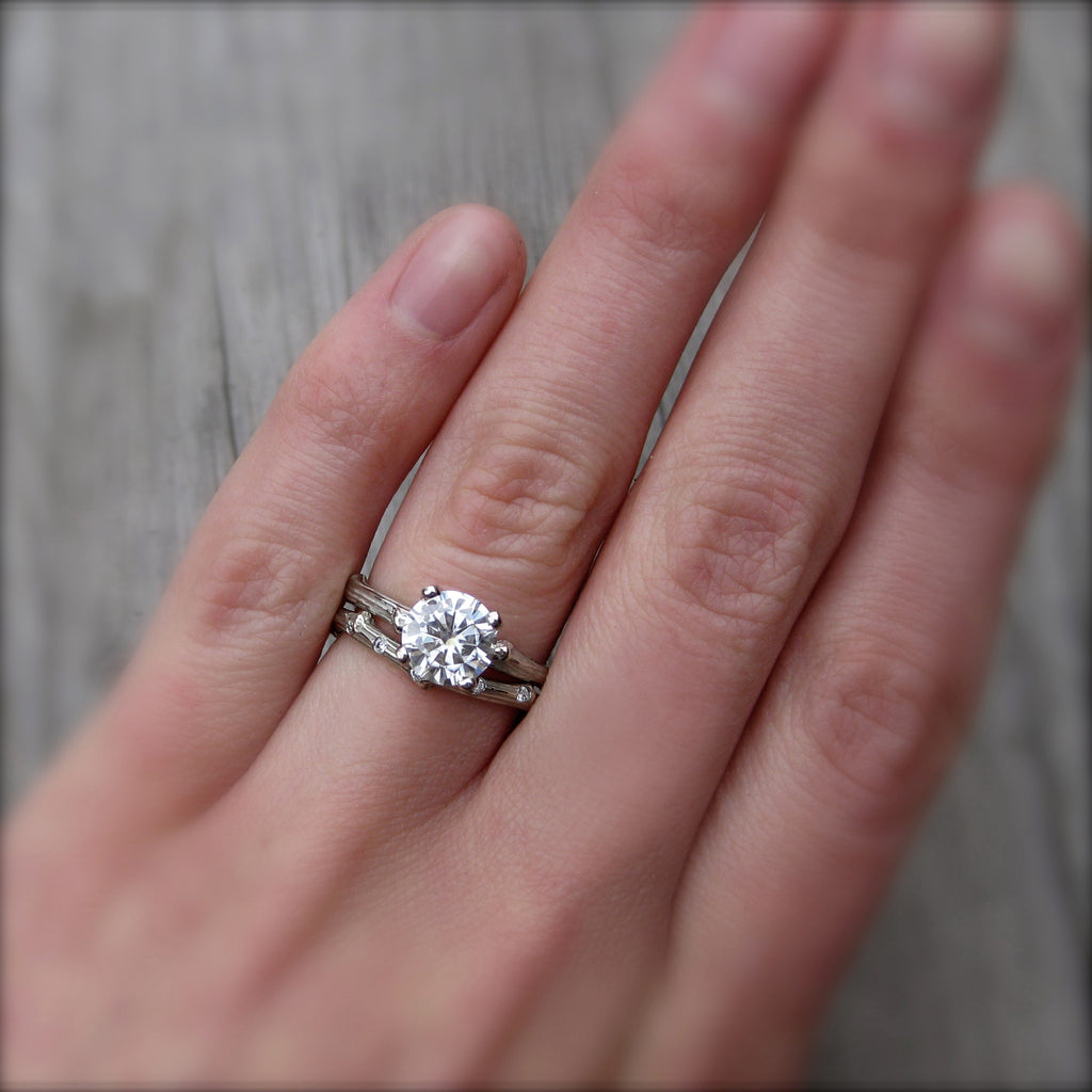Eco-friendly engagement ring with ethical diamond in 14k rose gold modeled on finger with stackable twig band