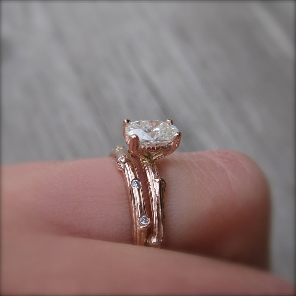 1ct Forever One oval cut moissanite engagement ring in 14k rose gold with a twig stackable wedding band