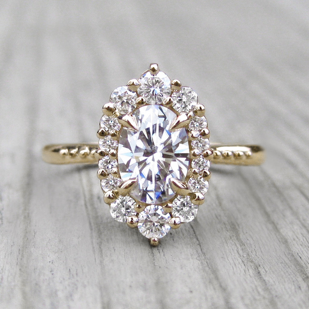 oval lab-created diamond halo engagement ring with a Canadian diamond halo in yellow gold
