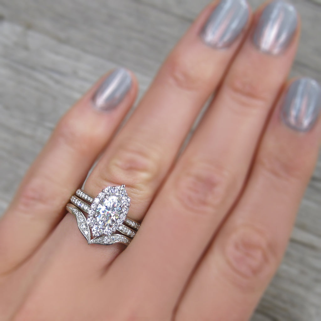 Antique-inspired and low-profile 1.5ct lab-grown oval diamond halo engagement ring stacked with two diamond wedding bands