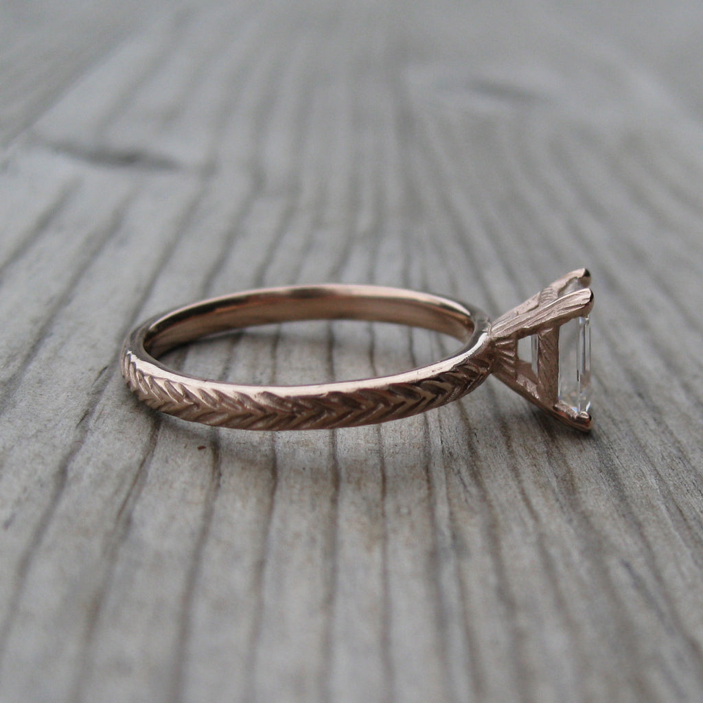 Eco Friendly feather ring with a Forever One emerald cut moissanite in rose gold
