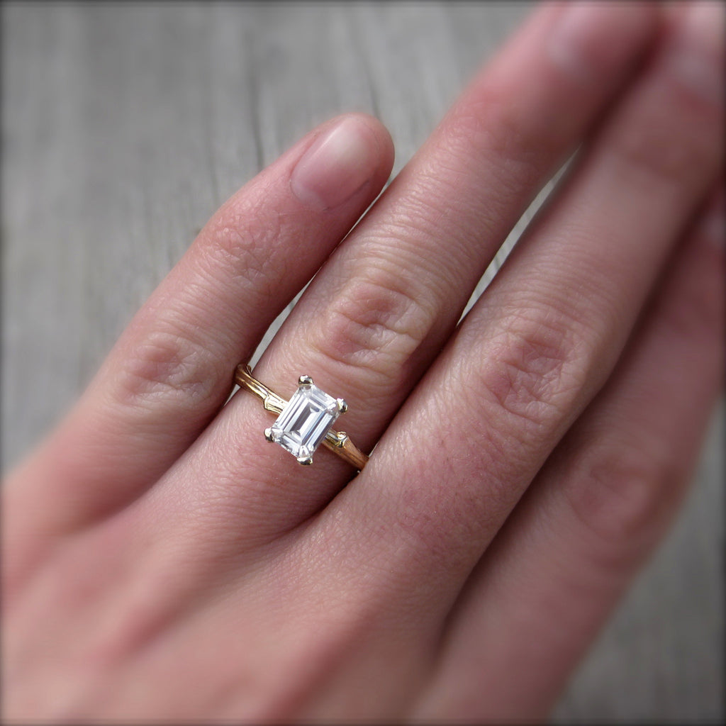 Rose gold twig solitaire engagement ring with a Forever One emerald cut moissanite