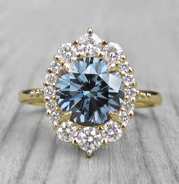 Antique-Inspired Blue-Grey Moissanite with a diamond halo in white gold