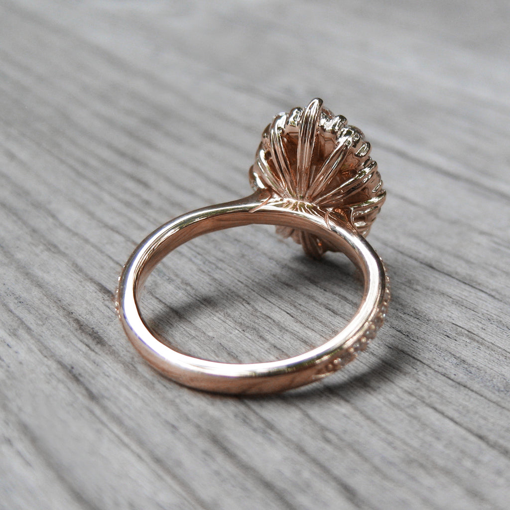 back side of blue-grey moissanite halo engagement ring with leaf-life gallery wires in rose gold