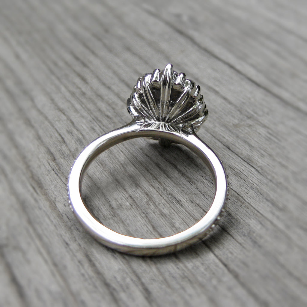 back side of blue-grey moissanite halo engagement ring with leaf-life gallery wires in white gold