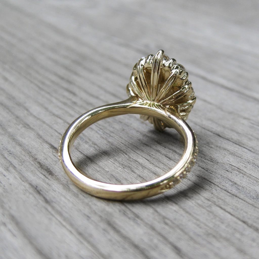 back side of blue-grey moissanite halo engagement ring with leaf-life gallery wires in yellow gold