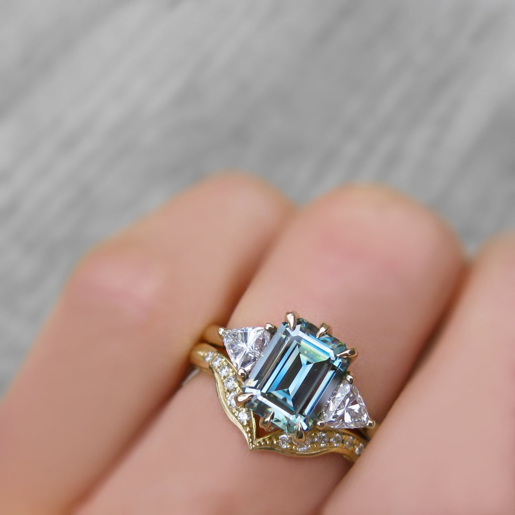 An emerald cut blue-green moissanite with a trillion side stones stacked with the twig textured V-Band