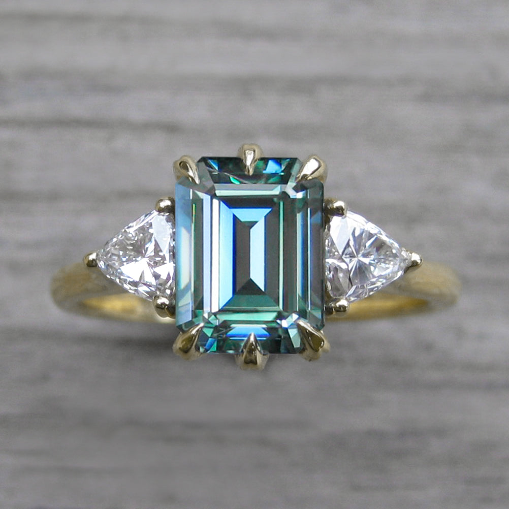 <center><strong>・AVERY・</strong><br></center>Teal Iconic™ Emerald Cut Moissanite Center, Trillion Diamonds (2.20ctw, Ready to Ship)