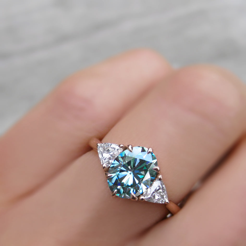 1.5ct oval engagement ring with a blue-green moissanite with trillion side stones