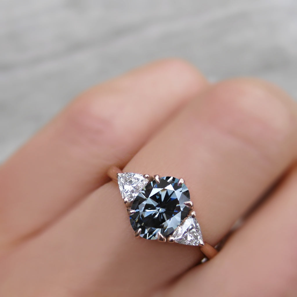 2ct three stone ring with an oval grey moissanite and lab-grown diamond trillion side stones