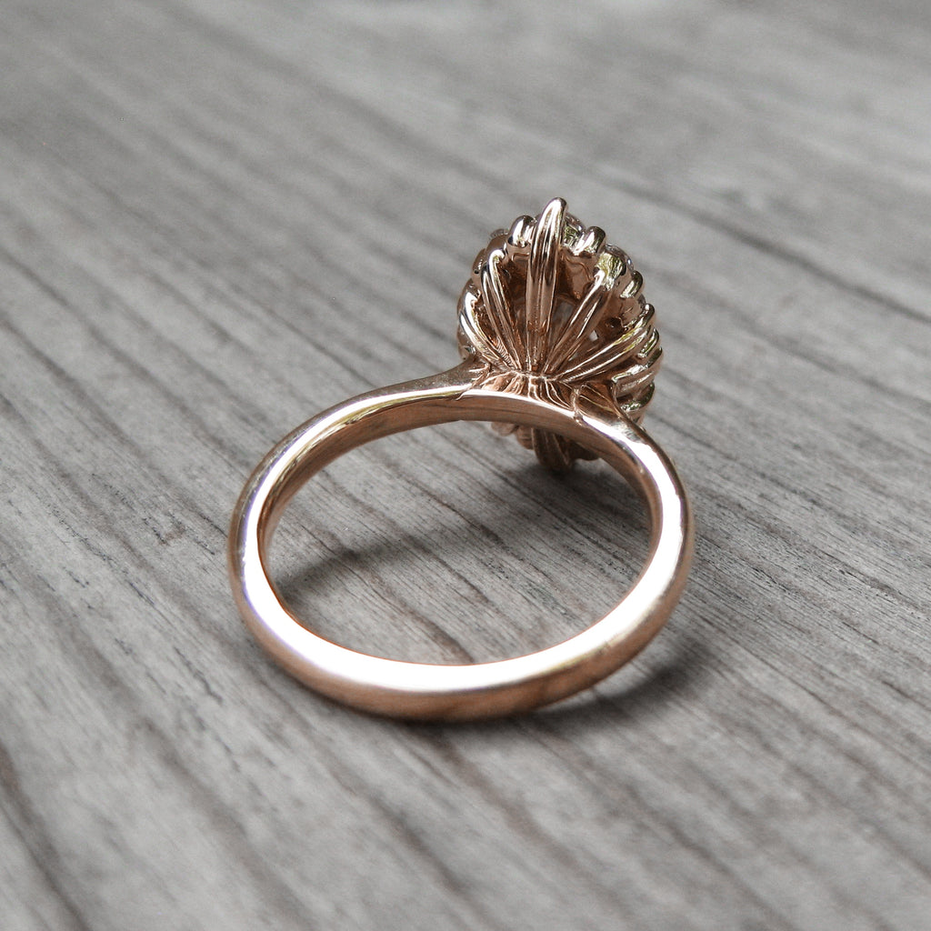 back side of oval sapphire halo engagement ring with leaf-life gallery wires in rose gold